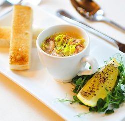 An image showing some toast, baby prawns in a cup with a slice of lemon on top of lettuce