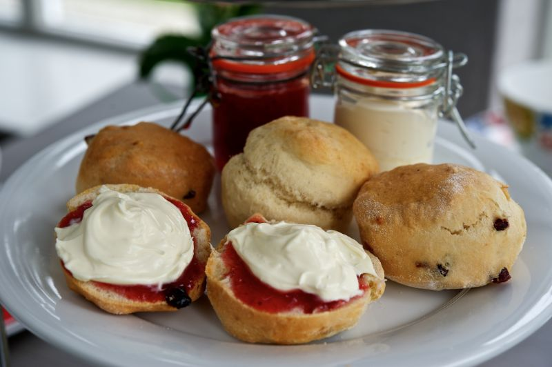 a selection of classic jam scones on a plate with jars of jam and cream