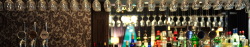 a row of glasses hung from the top of the lounge bar along with a selection of drinks and beer pumps
