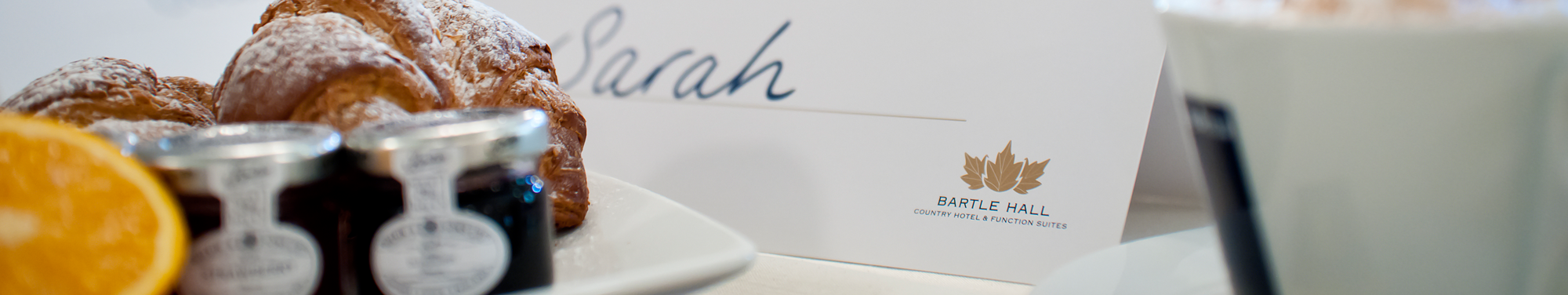 A close up image showing a table at breakfast with a sign, orange, croissants