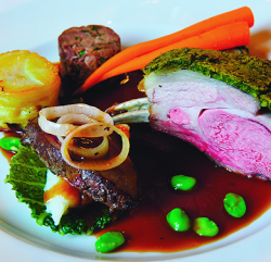 an image showing a plate of a Trio of Lamb – Roast Rack of Lamb with Herb Crust, Braised four hour Shoulder of Lamb and Lambs Liver and Onions with a Rosemary & Redcurrant Jus