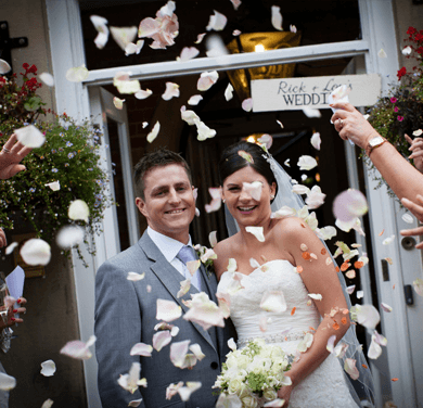 a bride and groom posing with confetti being thrown in the air just after getting married