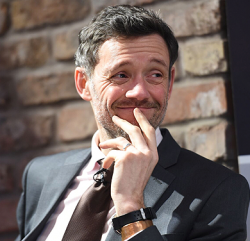 An image showing a man at an informal business meeting smiling with his fingers touching his chin.
