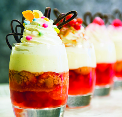 An image showing four Traditional English Sherry Trifles with Red Fruit, Thick Custard, Whipped Cream and Flaked Almonds