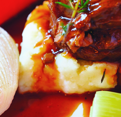 A close up image of a Shank of British Lamb Cooked Long & Low, sat on Creamy Mashed Potato, Fresh Mint Sauce