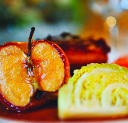 An close up image showing a Confit of British Pork with Cabbage Wedge, Roast Carrots, Little Roasties and Apple