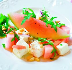 A plate showing Feta Cheese and Watermelon salad with Scattered Pine Nuts and Rocket