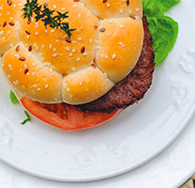 an overhead photo showing a tasty burger in a bun with salad on a plate