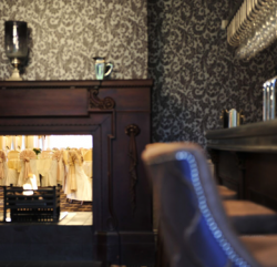 A close up image of a side of leather chair next to the bar area showing a warm and cosy fireplace in the background
