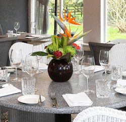 An image of a dinner table showing cutlery and plates with plant pot vase in the middle