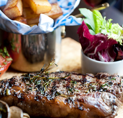 an image showing a picture of a steak, chips and salad