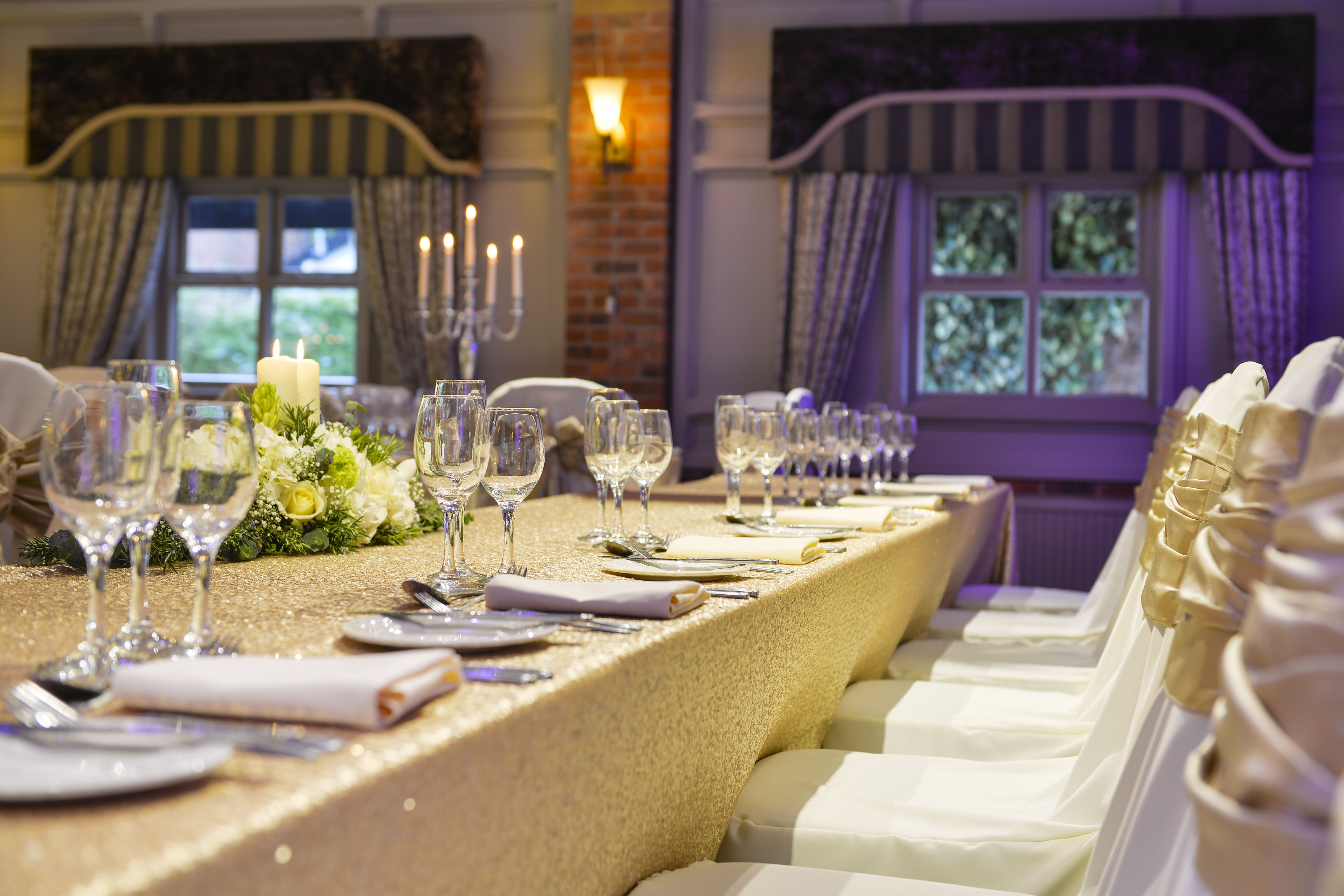 an angled shot of a head table at a wedding decorated with a lovely bouquet of flowers glasses and cutlery
