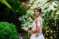 a bride holding a bouquet of flowers against a background of trees and bushes.