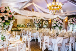 beautifully decorated wedding venue room showing tables and chairs with hanging drapes and chandeliers