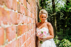 a bride leaning against a red brick wall holding a bouquet of flowers