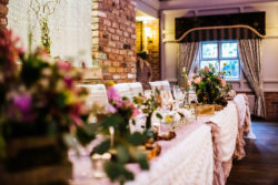 a table decorated with flowers by their wedding venue dressers