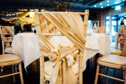 A close up image taken of a back of a decorated chair with a table in front from the Fairclough Studios open evening at Bartle Hall Country Hotel
