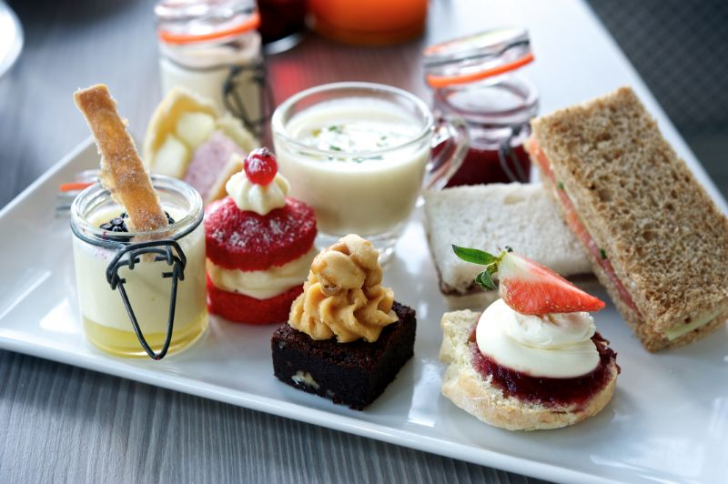a tray showing sandwiches with a selection of delicious cupcakes from their dining restaurant at Bartle Hall