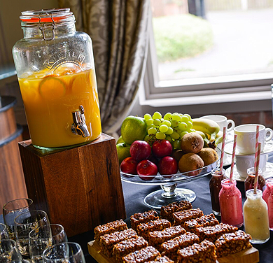 An image showing a jug of orange juice, a fruit bowl and cake refreshments in the hotel room